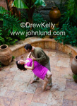 Stock photo of a multi-ethnic couple dancing alone together in an outdoor patio.  He is dipping her.  She is wearing a bright purple dress and has long black hair. They are both barefoot.